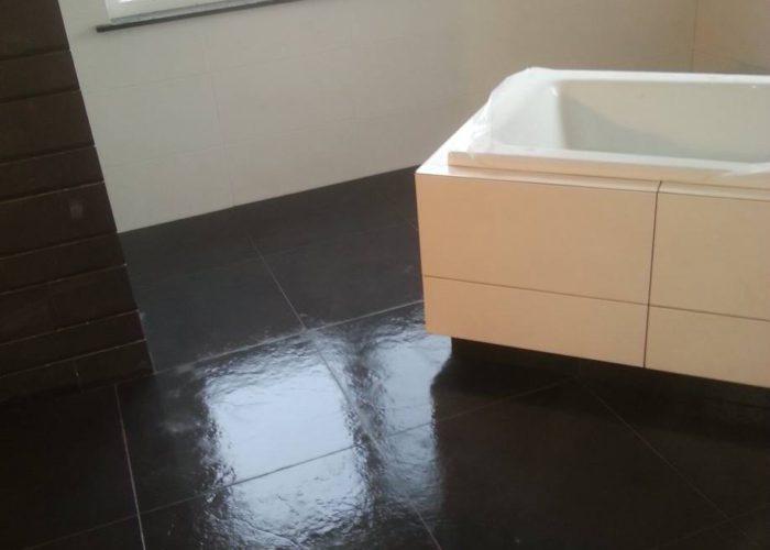 Nieuwbouw badkamer met mat witte tegels en decorstrip.